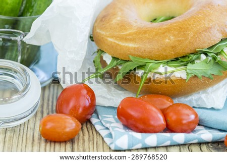Fresh bagel with a cream cheese and arugula or rocket salad filling surrounded by fresh vegetable ingredients including tomato, cucumber, and peppers on a rustic wooden table - stock photo