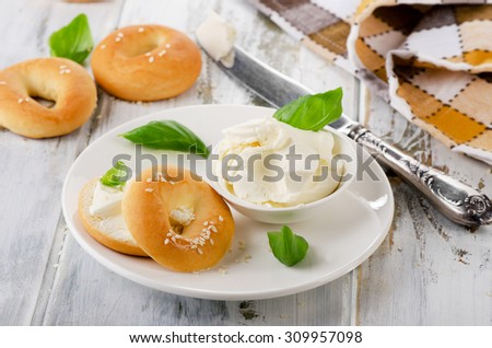 Fresh bagel with cream cheese for breakfast. Selective focus - stock photo