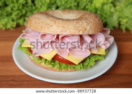 Fresh bagel with ham, tomatoes, cheese and lettuce - stock photo