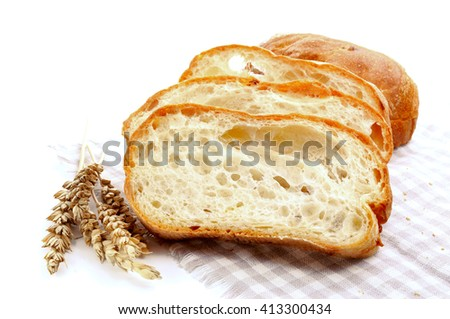 Fresh baguette bread and ripe ears of wheat - stock photo
