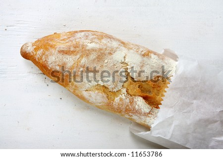 Fresh baguette in a white bakery bag, on rustic weathered white timber table.