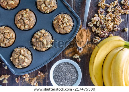 Fresh baked banana walnut and chia seed muffins sitting on wooden table with ingredients - stock photo