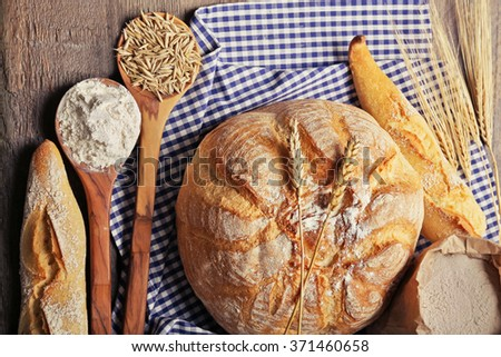Fresh baked bread, flour, wheat in spoons and napkin on the table, close-up - stock photo