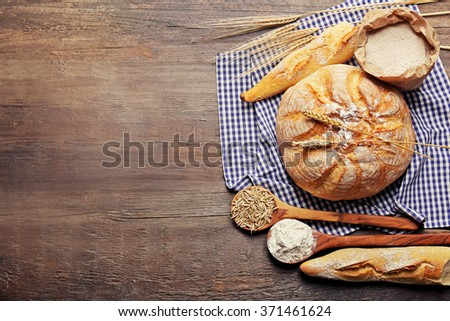 Fresh baked bread, flour, wheat in spoons and napkin on the wooden background - stock photo