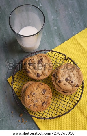 Fresh Baked Chocolate Chip Cookies on a Rustic Cooling Rack and Yellow Napkin with a Glass of Milk Shot from High Up. - stock photo