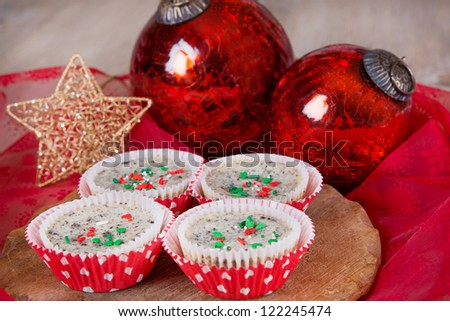 Fresh baked cookies and cream cheesecakes in muffin forms with red Christmas tree balls - stock photo