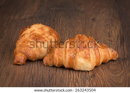 fresh baked croissant on a wooden background - stock photo