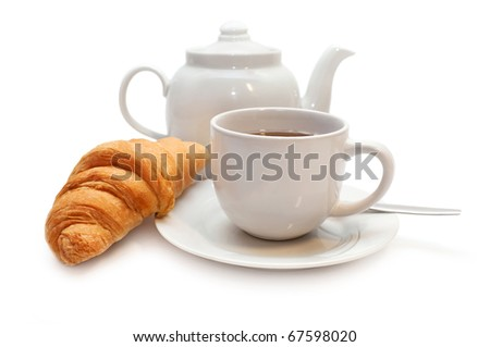 Fresh-baked croissant, teabag and cup of tea.
