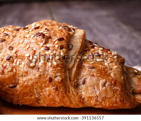 Fresh baked croissant with seeds on burlap on wooden table in rustic style