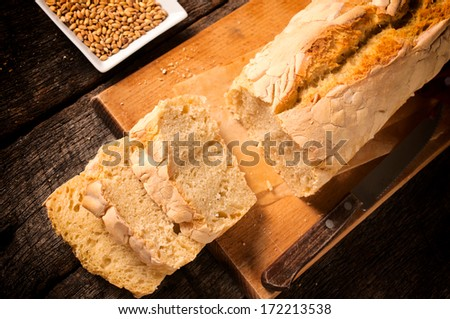 Fresh baked homemade bread on the wooden board.Selective focus on the bread slices - stock photo
