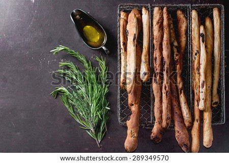 Fresh baked homemade grissini bread sticks in vintage metal grid box with olive oil and herbs rosemary and thym over dark surface. Top view. - stock photo