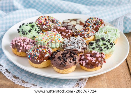 Fresh baked homemade mini donuts on a white plate - stock photo