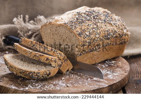 Fresh baked loaf of bread on rustic wooden background - stock photo