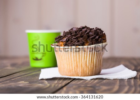 Fresh baked lunch delicious cupcake with chocolate pieces standing on white napkin near paper bright green glass of warm aromatic coffee refreshment bakery meal on wooden table light background