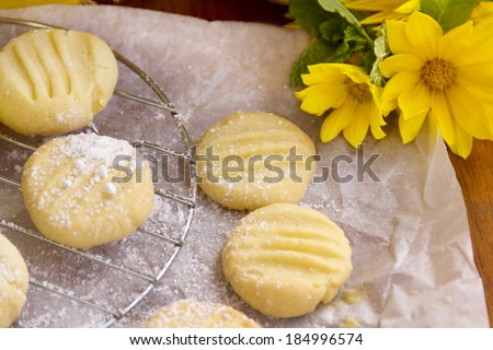 Fresh baked melting moments shortbread biscuits with icing sugar straight from the oven. - stock photo