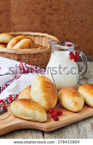 Fresh baked pasties and jug of milk - stock photo