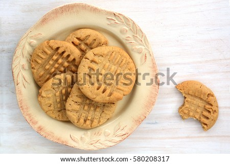 Fresh baked peanut butter cookies on rustic white background shot in natural light