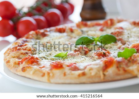 Fresh baked pizza with melted cheese, Italian herbs and tomato sauce and fresh basil on a white plate on a kitchen background, selective focus - stock photo