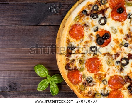 Fresh baked pizza with salami sausage and olives on dark brown wooden table