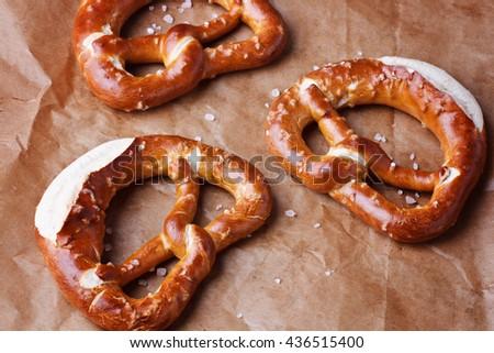 Fresh baked pretzels on baking paper close up - stock photo