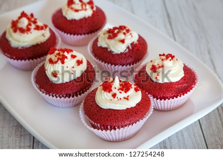 Fresh baked red velvet cupcakes with vanilla icing - stock photo