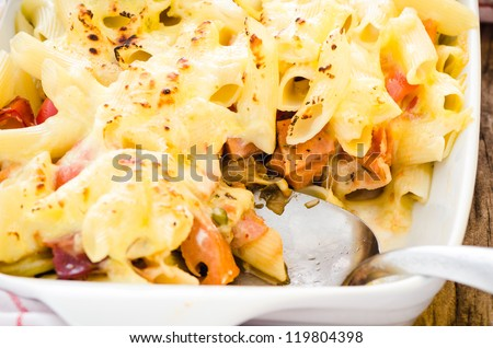fresh baked Rigatoni casserole with cheese sausage, bacon, tomatoes, cream and herbs - stock photo