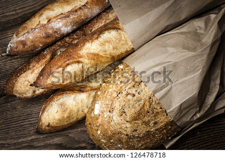 Fresh baked rustic bread loaves in paper bags on dark wood background - stock photo