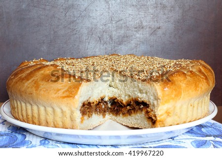 Fresh baked savory homemade round cabbage pie with cutting section, sliced, portion on the dark brown wooden background, just from oven, selective focus, close up - stock photo