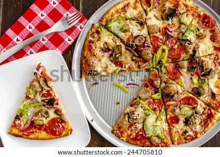Fresh baked slice of thin crust supreme pizza sitting on white plate with red heart napkin and fork - stock photo
