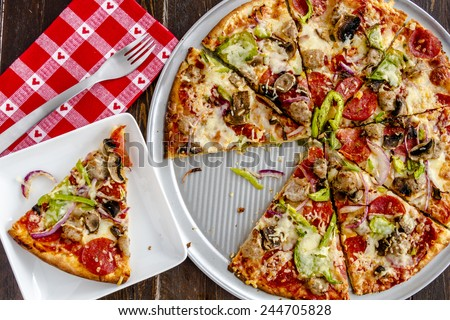 Fresh baked slice of thin crust supreme pizza sitting on white square plate with red heart napkin and fork - stock photo