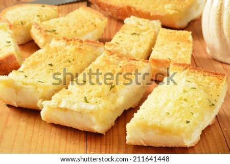 Fresh baked sliced garlic bread on a rustic wooden cutting board - stock photo