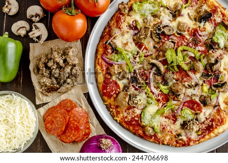 Fresh baked thin crust supreme pizza with fresh mushrooms, onions, green peppers, tomatoes, pepperoni, sausage and cheese - stock photo
