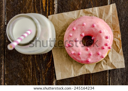 Fresh baked vanilla bean dough with pink icing sitting on wooden table with a glass of milk and pink striped straw - stock photo