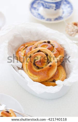 Fresh baked vanilla sweet sugar buns with chocolate drops in a bowl on a kitchen background  - stock photo