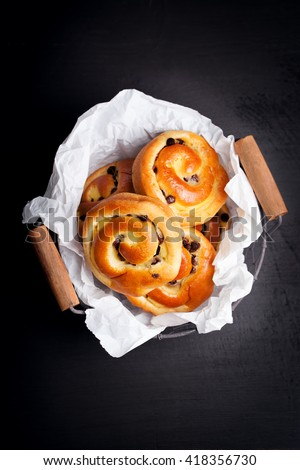 Fresh baked vanilla sweet sugar buns with chocolate drops in a crate on a black wooden background, top view, with free space for text, vertical - stock photo