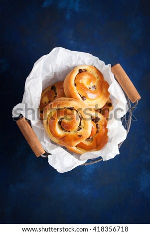 Fresh baked vanilla sweet sugar buns with chocolate drops in a crate on a blue wooden background, top view, with free space for text, vertical - stock photo