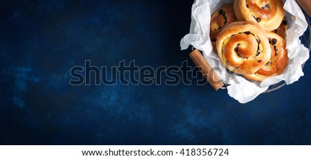 Fresh baked vanilla sweet sugar buns with chocolate drops in a crate on a blue wooden background, top view, with free space for text, horizontal - stock photo