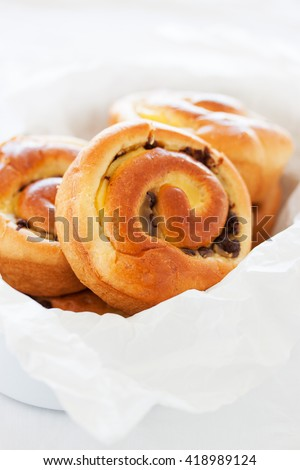 Fresh baked vanilla sweet sugar buns with chocolate drops in a crate on a wooden background, closeup - stock photo