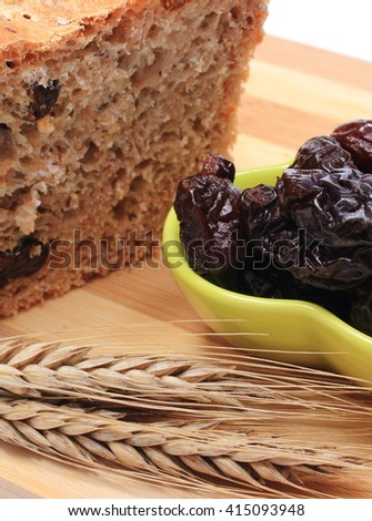 Fresh baked wholemeal bread, heap of dried plums and ears of wheat lying on cutting board, concept for healthy eating - stock photo