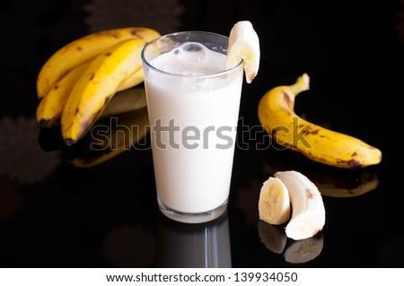 fresh banana smoothie and fruits on black background - stock photo