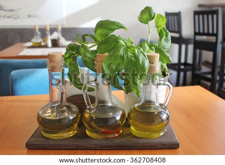 Fresh basil and olive oil in a carafe on the table - stock photo
