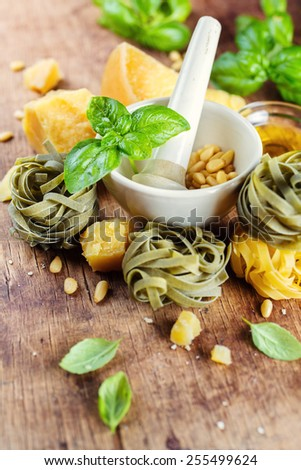 fresh basil in a mortar and ingredients for pesto - stock photo