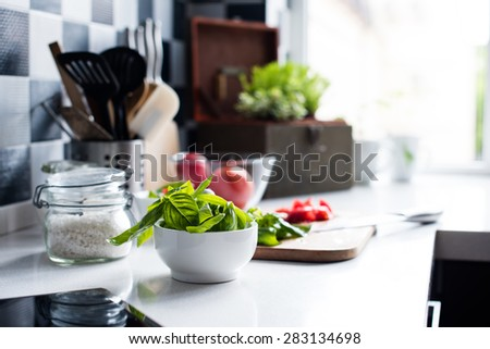 Fresh basil in a mortar, chopped tomatoes and ingredients for cooking on the kitchen table, the summer homemade Mediterranean cuisine. - stock photo
