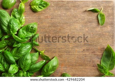 Fresh basil leaves on wooden board - stock photo