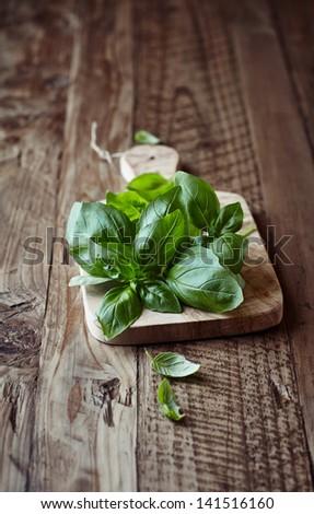Fresh basil on wooden chopping board - stock photo