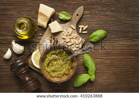 Fresh basil pesto ingredients on wooden background overhead shoot. - stock photo