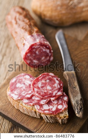 Fresh beef salami on wooden background close up - stock photo