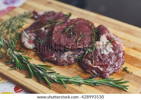 Fresh beef steak ready for BBQ cooking. Raw meat on a cutting board with rosemary leaf. Raw beef, veal meat on wood, closeup. Marinated in spices raw steak for barbecue. - stock photo