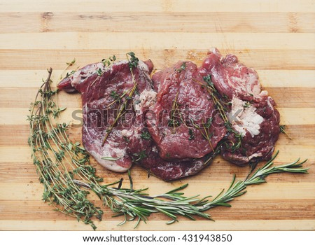 Fresh beef steak ready for BBQ cooking. Raw meat on a cutting board with rosemary leaf. Raw beef, veal meat on wood, closeup. Marinated in spices raw steak for barbecue. Top view - stock photo