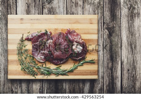 Fresh beef steak ready for BBQ cooking. Raw meat on a cutting board with rosemary leaf top view at rustic wood. Raw beef, veal meat on wood, closeup. Marinated in spices raw steak for barbecue. - stock photo